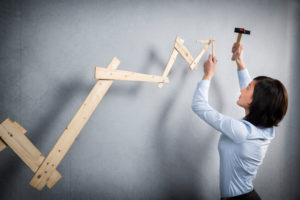 Confident woman building positive trend graph with hammer in hand.