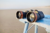 Binoculars reflecting a sunset and laying on table by the sea
